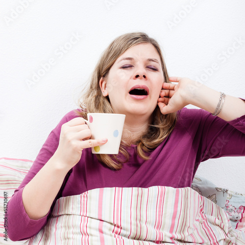 Woman with cup of coffee yawning