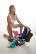 Female holidaymaker in underwear packing suitcase
