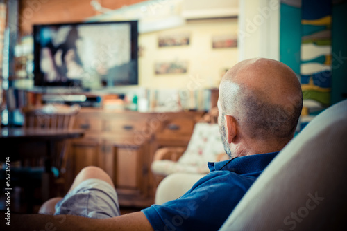 miggle age man watching tv