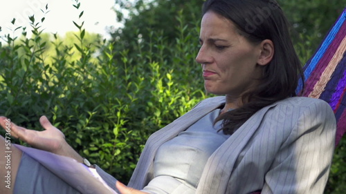 Angry businesswoman tossing documents on hammock, slow motion