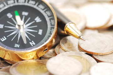 compass and pen on money background
