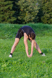 Young sportsman stretching before workout in park