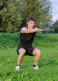 Young sportsman crouches before workout in park