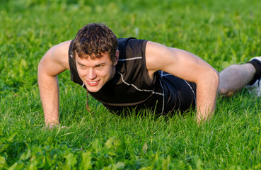 Handsome smiling man doing push-ups at the park
