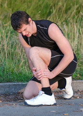 Sportsman holding his leg. Sports injury concept.