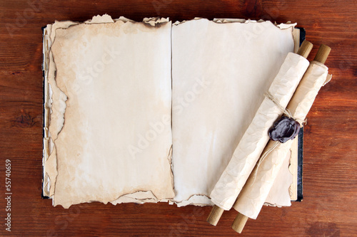 Open old book and scrolls on wooden background