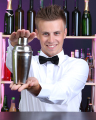 Portrait of handsome barman with shaker, at bar