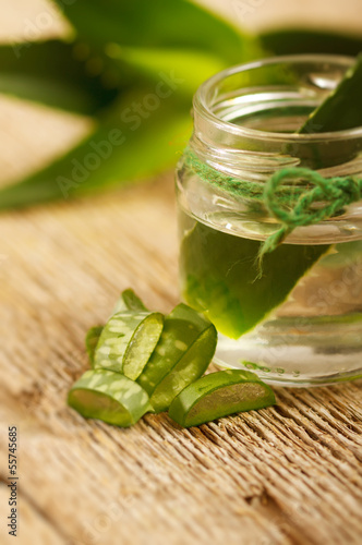 Extract of organic aloe vera gel on wooden background