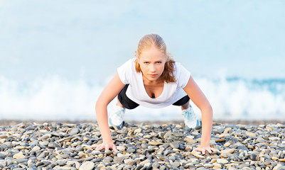 Young healthy woman playing sports push-ups outdoors on the beac