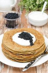 potato pancakes with sour cream and caviar on a plate
