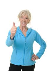 Sportliche Seniorin mit Daumen nach oben