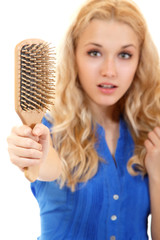 women with hair broblem holding loss hair comb in hand