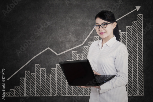 Attractive female holding laptop on profit bar chart