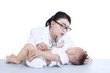 Beautiful female doctor checkup baby - isolated