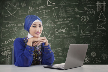 Beautiful female muslim with laptop in class