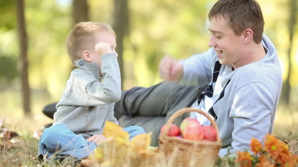 Father with son playing outdoors in autumn park