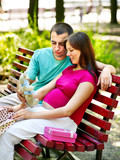 Pregnant woman with man outdoor.