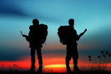 Silhouette of two men of backpacker tourists
