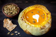 Pumpkin soup baked in a pumpkin on a wooden background