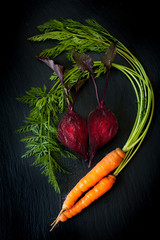 Beetroot and carrots on a black slate chalkboard
