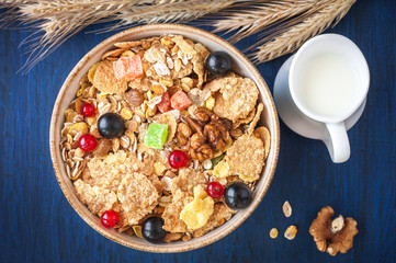 Cereal muesli (granola) in a bowl with berries and milk