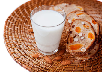 Grain bread with dried fruit, nuts and a glass of milk.
