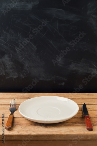 Empty plate on wooden table over chalkboard background