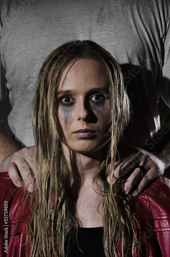 abused woman with man standing behind her vertical