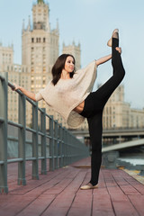 Young woman makes a stretching leaning on the railing