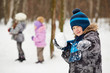 Portrait of boy which aims with snowball screwing up one eye