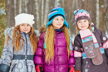 Three girls-friends stand in winter park