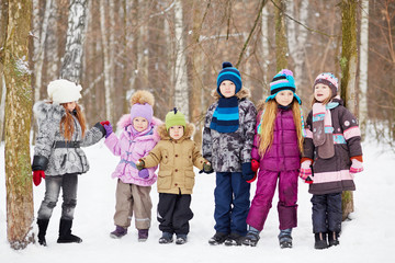 Six children  stand holding hands in winter park