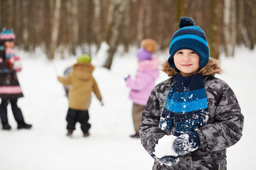 Portrait of boy who stands in winter park and holds snowball
