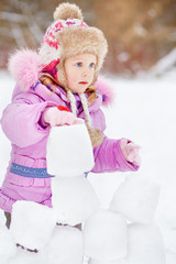 Portrait of little girl who builds wall of snow blocks in winter