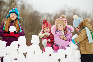 Girl build wall from snow bricks with three little children
