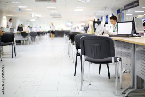 Men and women work at computers in car dealership office.