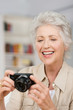 lächelnde seniorin mit digital kamera