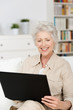 lächelnde ältere frau schaut auf laptop