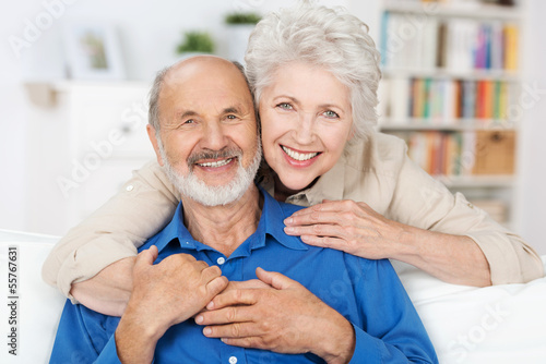 glückliches älteres paar umarmt sich auf dem sofa - 55767631