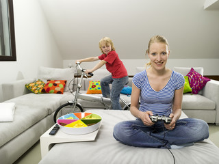 Mutter und Sohn im Wohnzimmer, Mutter spielt Computerspiele