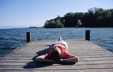 Junger Mann entspannt auf Steg, Erhöhte Ansicht