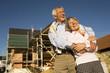 Älteres Paar umarmt sich vor Baustelle