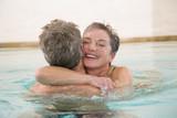 Älteres Paar umarmt sich im Schwimmbad, Porträt