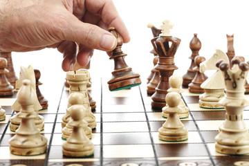Mann bewegt Läufer auf Schachbrett