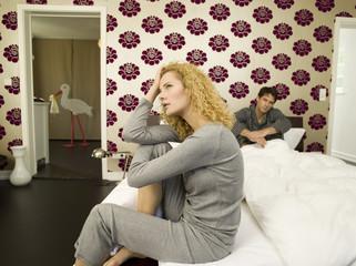 Junges Paar, Frau sitzt auf der Kante des Bettes