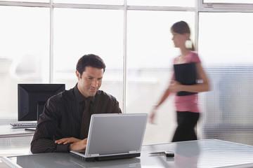 Mann arbeitet an Laptop, Frau im Hintergrund