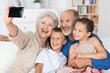 großeltern fotografieren die familie mit handy
