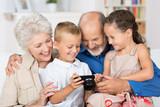 großeltern und enkel schauen auf digitalkamera
