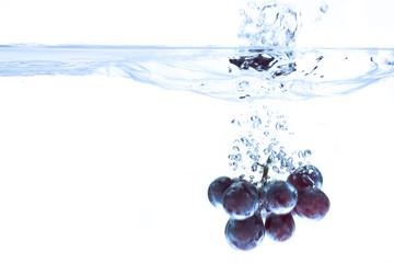 Rote Trauben ins Wasser fallen, Wasser spritzt