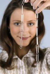 Junge Frau mit Büroklammer-Kette, lächelnd, Nahaufnahme